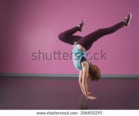 Pretty break dancer doing a handstand in the dance studio - stock photo