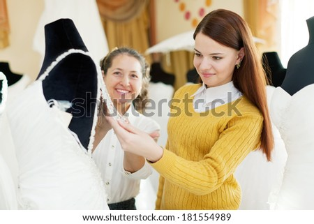 pretty bride chooses bridal outfit at shop of wedding fashion. Friendly shop consultant helps her - stock photo
