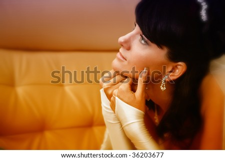 Pretty bride with is laying on the leather sofa. Focus point on the face.