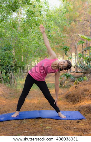 pretty brown hair girl standing in park and is relaxing with yoga