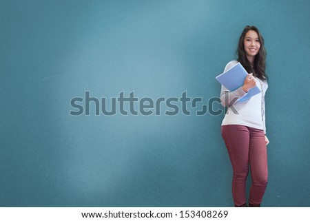 Pretty brown haired student posing on blue background - stock photo