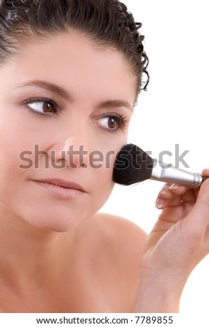 Pretty brunette applying foundation to her face
