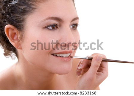 Pretty brunette applying lipgloss to her lips - stock photo