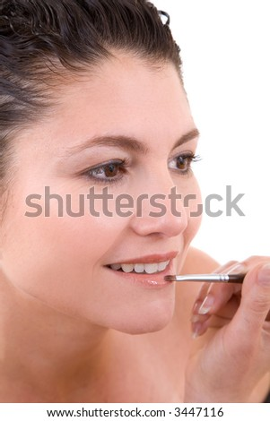 Pretty brunette applying lipstick to her lips with a small brush on white background