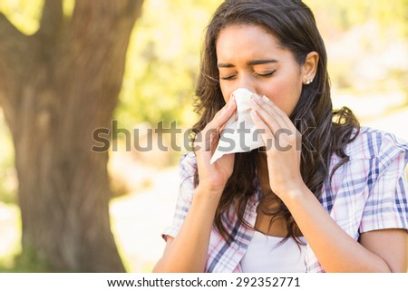 Pretty brunette blowing her nose on a sunny day