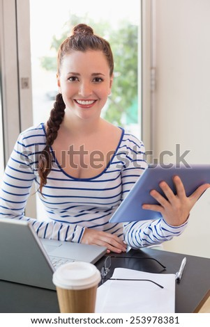 Pretty brunette catching up on work at the cafe - stock photo