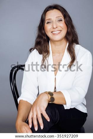 pretty brunette confident mature woman sitting on chair in studio smiling tender mulatto - stock photo