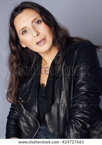 pretty brunette confident stylish real mature woman sitting on chair in studio, sexy on gray background wearing leather jacket - stock photo