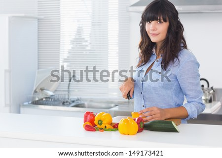 Pretty brunette cutting pepper at kitchen counter - stock photo