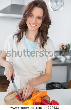Pretty brunette cutting peppers in her kitchen  - stock photo