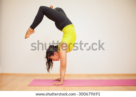 Pretty brunette doing a headstand with crossed legs during practice in a yoga studio