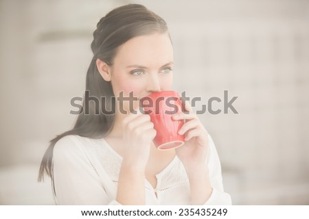 Pretty brunette drinking cup of coffee at home in the living room - stock photo