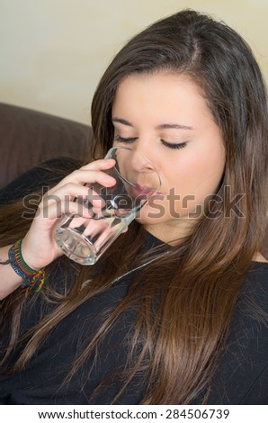 pretty brunette drinking from a glass pf water while sitting in sofa