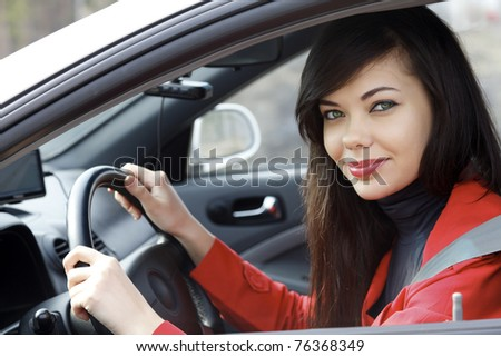 Pretty brunette driving a car - stock photo