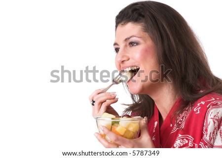 Pretty brunette eating a bowl of fruit on white background