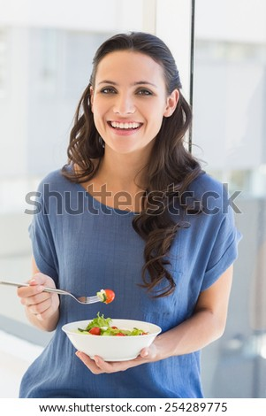 Pretty brunette eating a salad at home beside window - stock photo