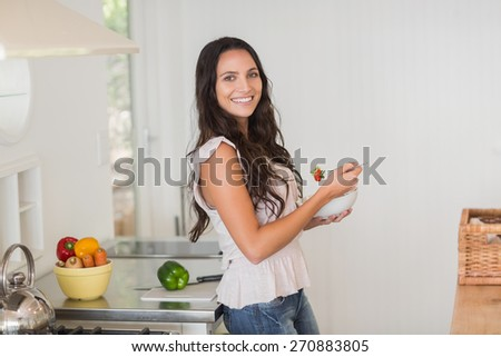 Pretty brunette eating a salad in the kitchen - stock photo