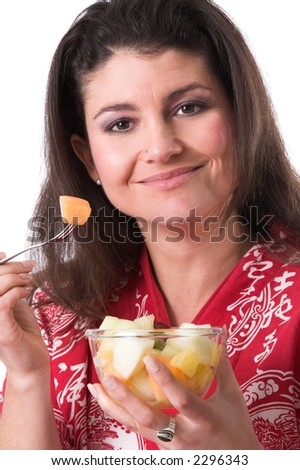 Pretty brunette eating from a bowl of fresh fruit - stock photo