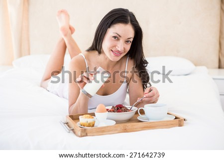Pretty brunette eating her breakfast on bed at home - stock photo