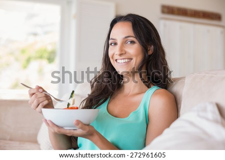 Pretty brunette eating salad on couch at home in the living room - stock photo