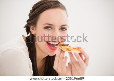 Pretty brunette eating slice of pizza at home in the kitchen