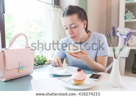 Pretty brunette eating sweet meringue in french cafe. Beautiful young woman eating tartelette and drinking coffee. Attractive funny girl smiling.  - stock photo