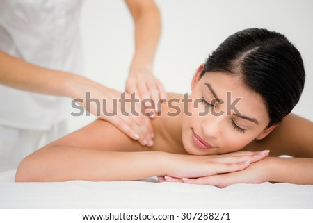 Pretty brunette enjoying a massage at the health spa - stock photo