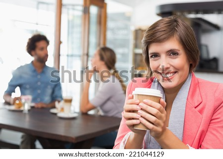 Pretty brunette enjoying her coffee at the coffee shop - stock photo