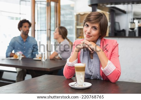 Pretty brunette enjoying her latte at the coffee shop - stock photo