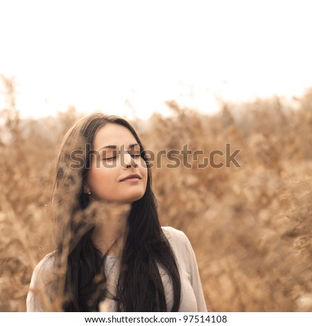 Pretty brunette enjoys the freshness of the morning - stock photo