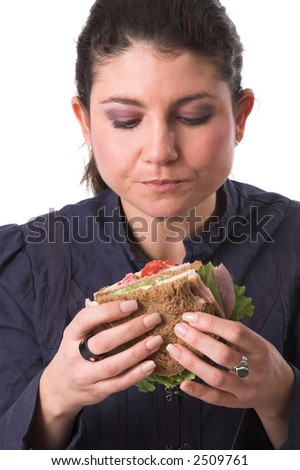 Pretty brunette focused completely on her healthy tasty sandwich, ready to take a bite - stock photo