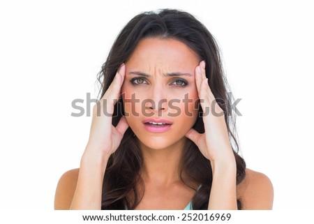 Pretty brunette getting a headache on white background - stock photo