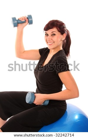Pretty brunette girl doing healthy exercise with dumbell weights and exercise ball