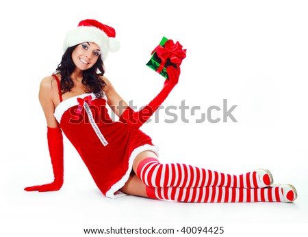 pretty brunette girl dressed as Santa with a Christmas present - stock photo