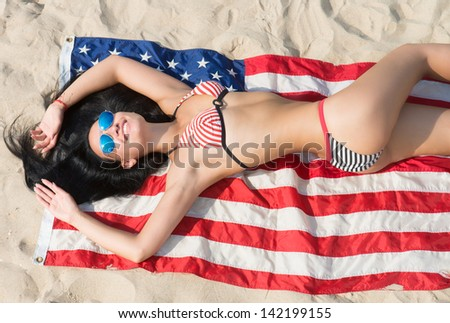 Pretty brunette girl in bikini and blue sunglasses lying on the American flag on the sand beach, view from above - stock photo
