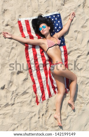 Pretty brunette girl in bikini lying on the American flag on the sand beach, view from above - stock photo