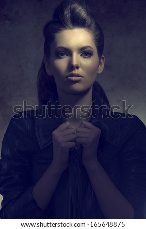 pretty brunette girl in dark portrait with curly hair-style, modern style wearing leather jacket and looking in camera  - stock photo