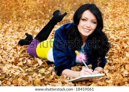 pretty brunette girl in the park with a pen and a note-book - stock photo
