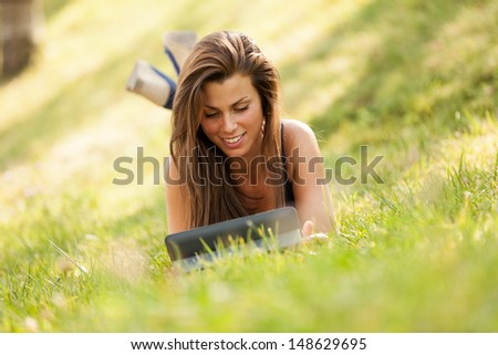 Pretty brunette girl is looking a digital screen while sitting on the grass and smiling