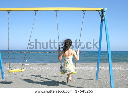 Pretty brunette girl on the swings at the sea.