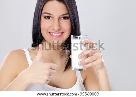 pretty brunette girl with a glass of milk and her thumb up - stock photo