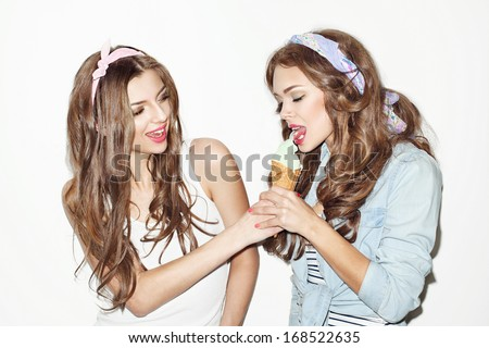 Pretty brunette girls with bright makeup and pink lips having fun. One keeping green ice cream with her hand other trying it. Inside - stock photo