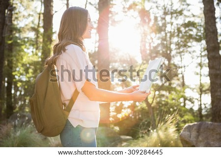 Pretty brunette hiker reading map in the nature - stock photo