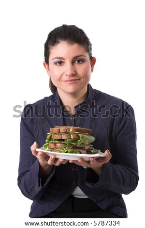 Pretty brunette holding a plate with a healthy sandwich - stock photo
