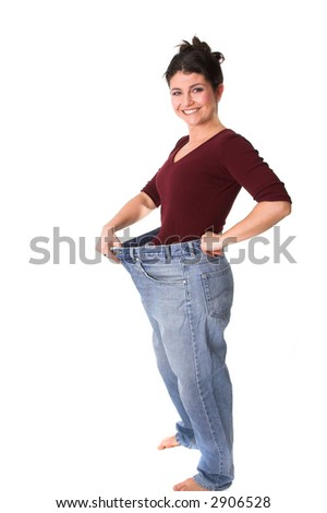 Pretty brunette holding out her old jeans who are now too wide - stock photo