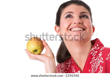 Pretty brunette holding up an apple with a big smile on her face - stock photo