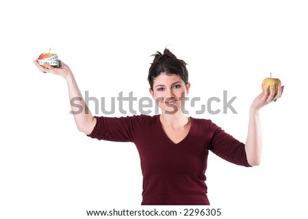 Pretty brunette holding up two apples as if on a measuring scale - stock photo