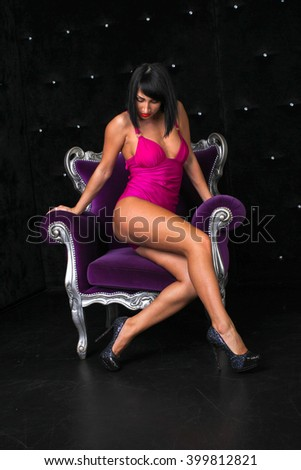 Pretty brunette in red underwear posing in studio with violet chair - stock photo