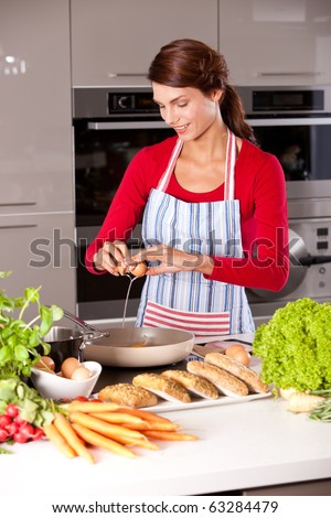Pretty brunette in the kitchen baking an egg in the frying pan - stock photo