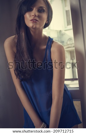 pretty brunette lady posing near window in indoor shoot and wearing sexy blue babydoll  - stock photo
